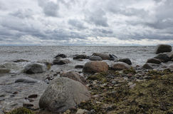 Beach wavy Baltic Sea with boulders. Cloudy summer evening wind against a dark cloudy sky stock images