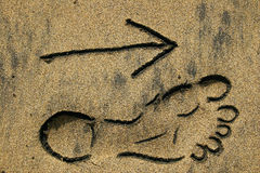 Beach This Way. Footprint outline and arrow on the beach Royalty Free Stock Photo
