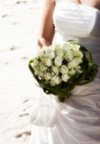 Beach wedding. Close up on white roses bouquet and dress of bride with beach sand in background Royalty Free Stock Images