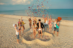 Beach wedding. Of happy newlywed couple around their friends royalty free stock photo