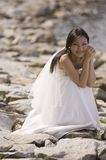 Beach Wedding. A bride poses by the edge of a rocky seashore in her wedding dress Royalty Free Stock Photos
