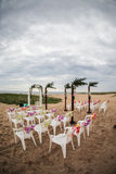 Beach wedding. Chairs and wedding arbor on a breezy beach Stock Images