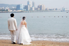 Beach wedding. Bride and Groom Walking on the Beach Royalty Free Stock Photo
