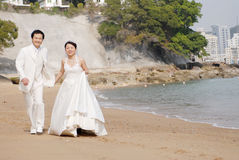 Beach wedding. Bride and Groom Walking on the Beach Royalty Free Stock Image