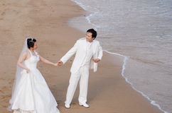 Beach wedding. Bride and Groom Walking on the Beach Stock Photo