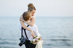 Beach wedding: bride and groom by the sea. Beach wedding: bride and groom hugging by the sea Royalty Free Stock Images