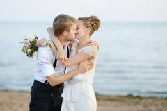 Beach wedding: bride and groom by the sea Royalty Free Stock Photo