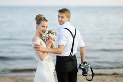 Beach wedding: bride and groom by the sea. Beach wedding: bride and groom hugging by the sea Royalty Free Stock Photo