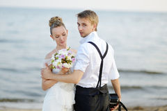 Beach wedding: bride and groom by the sea. Beach wedding: bride and groom hugging by the sea Stock Images