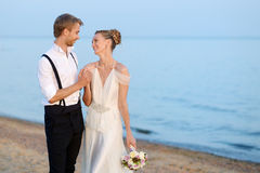 Beach wedding: bride and groom by the sea Stock Images