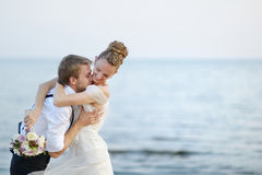 Beach wedding: bride and groom by the sea. Beach wedding: bride and groom hugging by the sea Royalty Free Stock Image