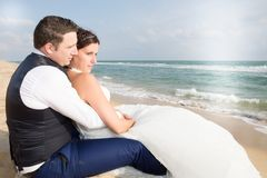 Beach wedding bride and groom by the sea sit on sand ocean. Beach Royalty Free Stock Images