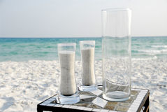 Beach wedding ceremony. A view of glass vases and sand sitting on a small table on a beach in preparation for a beach wedding ceremony Stock Photos