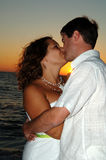 Beach wedding couple kiss. A bride and groom kissing on the beach after wedding at sunset Stock Photos