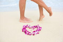 Beach wedding rings with kissing couple feet Royalty Free Stock Photos