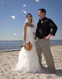 Beach wedding throwing flowers. A  happy bride and groom on the beach after wedding with flower petals being thrown in celebration Stock Photos