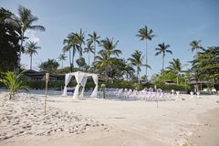 Beach wedding venue arrangement at seaside, Arch, Altar with minimal flowers decoration, palm tree and coconut background stock photography