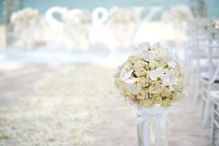A bunch of white cream roses, orchids on the glass vase beside the aisle at the beach wedding ceremony - closed up. The beach wedding venue decoration, on the royalty free stock photos