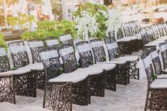 Beach wedding wooden chairs arrangement for wedding venue on the sand. A group of black weave wooden chairs with white sash decoration and cone of rose petals Stock Photos