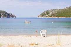 Beach with a white fishing chair and a tied fishing boat at Porto Koufo harbor Royalty Free Stock Photos