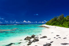 Beach with white sand and black rocks on Rarotonga, Cook Islands. Amazing beach with white sand and black rocks on Rarotonga, Cook Islands Royalty Free Stock Photography