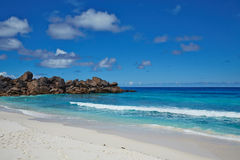 Beach with white sand, blue ocean and stones, Seychelles Stock Photo