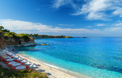 Beach with white sand and clear blue water in beautiful Bay with sun beds and umbrellas, Crete, Greece Stock Images