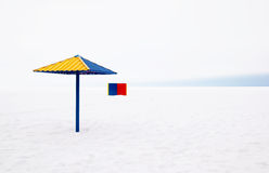 On the beach in winter. Umbrella and cabin on a snowy beach on the Gulf of Finland Stock Photos
