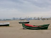 Beach in winter with boats on the sand with in distance  cranes  of a shipyard to Valencia in Spain. Stock Photos