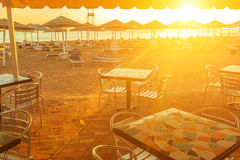Beach With Deck Chairs, Parasol, And Bar During Sunrise Stock Image