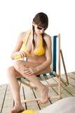 Beach - woman in bikini apply suntan lotion Royalty Free Stock Images