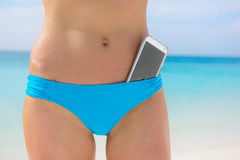 Beach woman bikini bottom - smartphone app concept. Beach woman bikini bottom. Lower body crop with smartphone screen in focus. Mobile phone in swimwear bathing Royalty Free Stock Photography