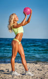 Beach woman in bikini holding a volleyball Stock Image