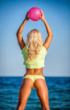 Beach woman in bikini holding a volleyball Royalty Free Stock Images