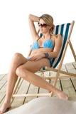 Beach - woman in bikini sitting on deck chair. Beach - Young woman in bikini sitting on deck chair relaxing Royalty Free Stock Image