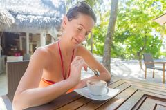 Woman in bikini enjoying coffee at outdoors bar, tropical background. Beach woman drinking cold drink beverage having fun at beach party. Female babe in bikini royalty free stock images
