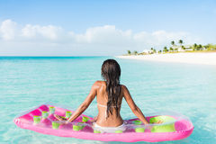 Beach woman floating on ocean water pool mattress. Beach relaxation woman floating on pink inflatable air bed pool mattress toy float in ocean beach background Stock Photos