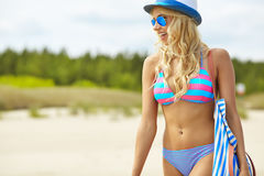 Beach woman funky happy. And colorful wearing sunglasses and beach hat having summer fun during travel holidays vacation royalty free stock images