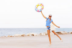 Beach woman happy and colorful wearing sunglasses and beach hat having summer fun during travel holidays.  Stock Photo