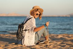 Beach woman happy and wearing sunglasses and beach hat having summer fun during travel holidays vacation royalty free stock images