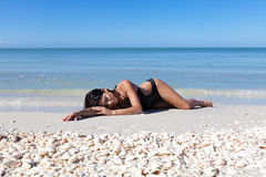 At the beach. Woman laying at the beach royalty free stock image