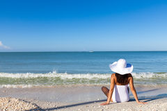 At the beach. Woman sitting at the beach stock image