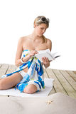 Beach - woman sitting with book, sunbathing Stock Photo