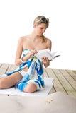 Beach - woman sitting with book, sunbathing Stock Photo