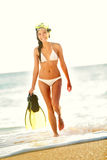 Beach woman snorkeling walking happy. Enjoying sun and holidays travel in sunny sunshine wearing bikini holding snorkel, fins and mask. Beautiful excited mixed Stock Image