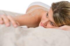 Beach - woman sunbathing on sand. Lying down Stock Image