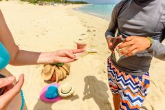 On the beach a woman in a swimsuit pays money for bought hats fr stock photo