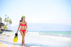 Beach woman walking by ocean - bikini and snorkel. Beach woman walking by ocean. Girl in bikini with snorkel coming out of water after swimming and snorkeling in Royalty Free Stock Image