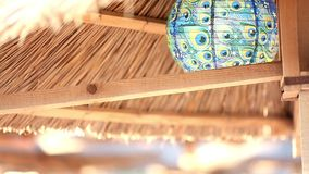 Beach wood umbrella with turquoise lamp at daytime Royalty Free Stock Photos