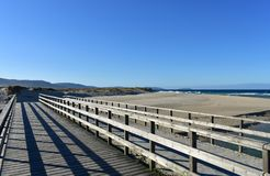 Beach with wooden boardwalk, dunes and wild sea with waves. Blue sky, Galicia, Spain. stock photography